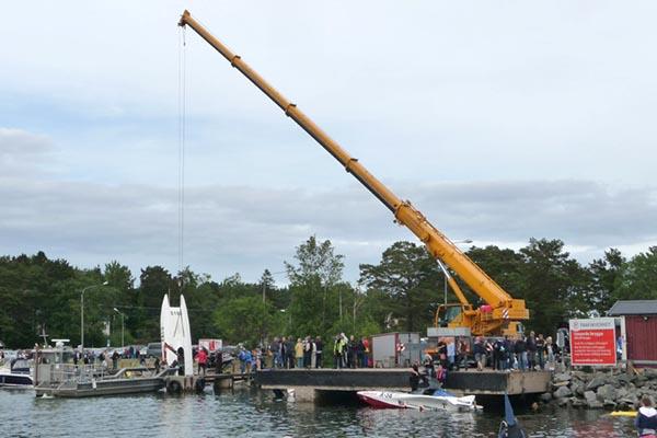 Lyftkran lyfter upp en båt ur vattnet